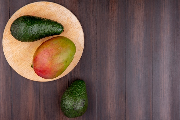 Top view of mango with avocado on a wooden kitchen board on a wooden surface