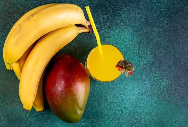 Mango vista dall'alto con banane e succo d'arancia con una cannuccia gialla su verde