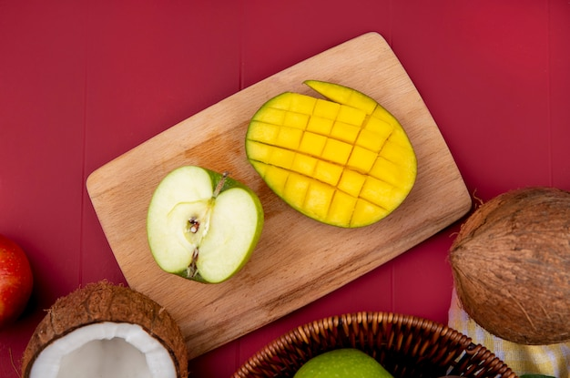 Top view of mango with halved green apple on a wooden kitchen board on red surface