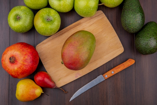 Top view of mango on a wooden kitchen board with knife with apples pomegranate on a wooden surface