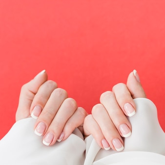 Top view manicured hands on vibrant pink background