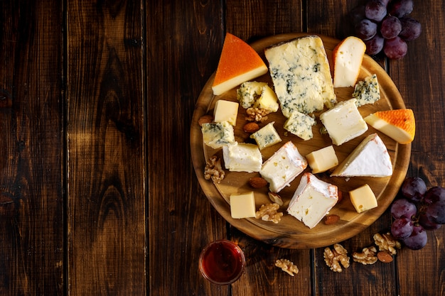 Top view of many cheese sorts served on wooden board