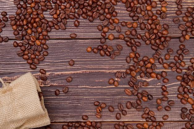 上から見ると、袋からこぼれた多くのコーヒー豆。素朴な木の表面。