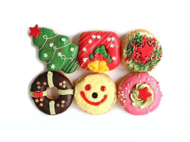 Top view of many colorful christmas decorated doughnuts sweets isolated on white background