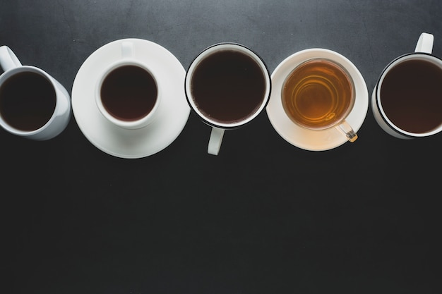 Top view of many cups, mugs with hot tea drink on dark , copyspace. tea time or tea brake. autumn toned, dark photo.