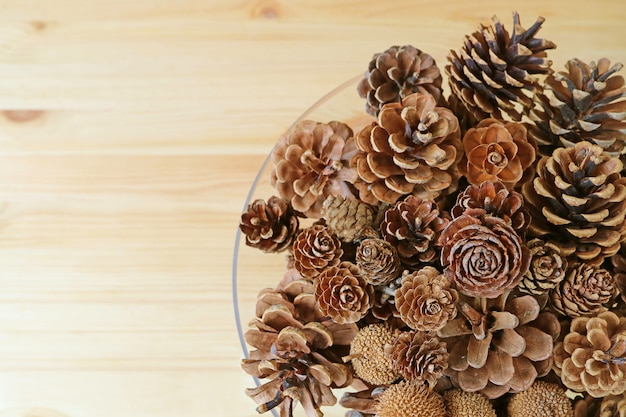 Top view of many different type and different size of natural dry pine cones in a glass bowl