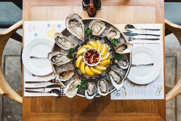 Top view many kinds of fresh oysters served in round tray with slice lemon and spicy sauce.