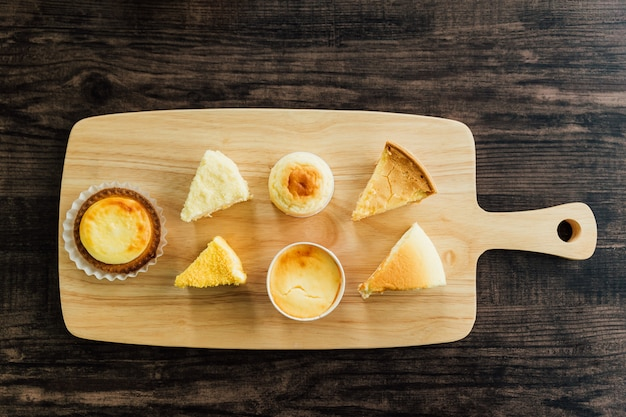 Top view many kinds of mascarpone crème brulee cheesecake slices, cheese tarts on wooden chopping board, smooth, rich milky taste.