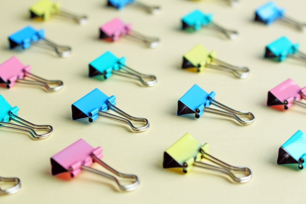 Top view of many multicolor binders clips on pastel beige background.