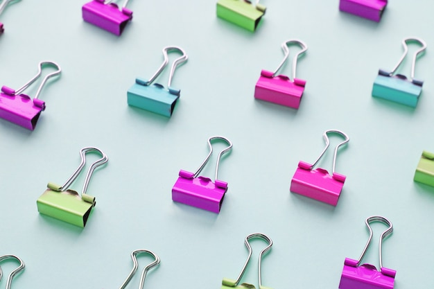 Top view of many multicolor binders clips on pastel blue background.trendy neon colors.