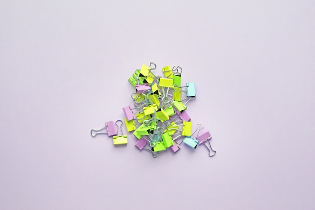 Top view of many multicolor binders clips on pastel purple background.trendy neon colors.