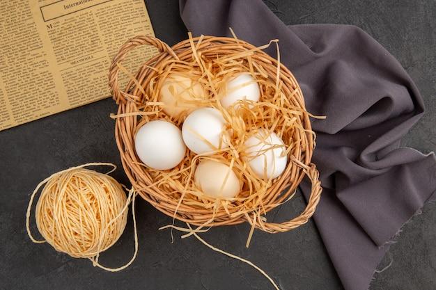 Vista dall'alto di molte uova organiche in un cesto su un vecchio giornale su asciugamano nero e corda su superficie scura