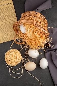 Vista dall'alto di molte uova organiche all'interno e all'esterno di un cesto su un vecchio giornale su un asciugamano nero su una superficie scura
