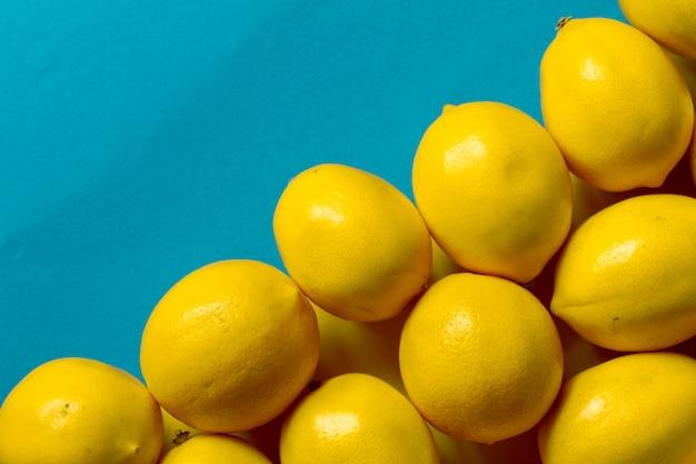 青い表面、背景または概念上の多くの熟したレモンのトップビュー