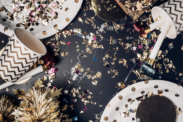 Top view marble table with party cup,party blower,tinsel,confetti