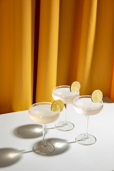 Top view of margarita cocktail glasses with salty rim and lime on white table