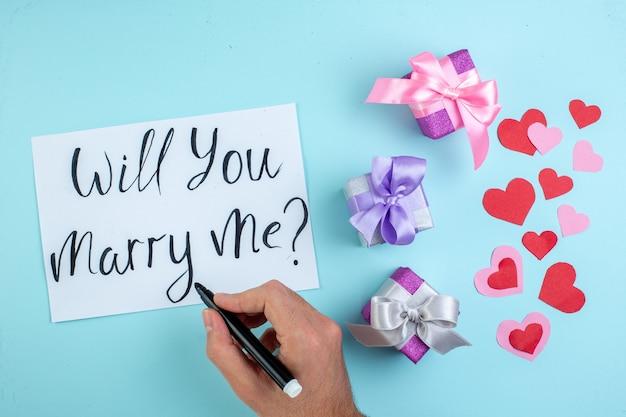Маркер вид сверху в мужской руке, выйдешь за меня замуж, написано на бумаге, красные и розовые сердечки, подарки на синем фоне