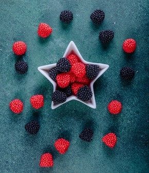 Top view marmalade in the form of blackberries and raspberries in a socket for jam in the shape of a star on a dark green background