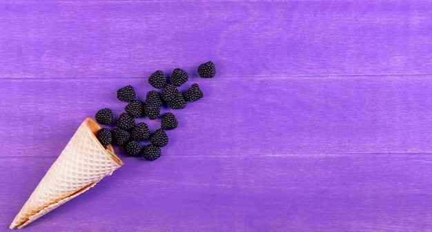 Top view marmalade in the form of a blackberry with a waffle cone on a purple background