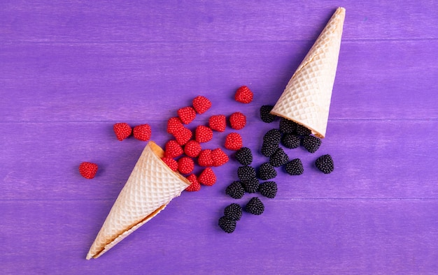 Top view marmalade in the form of raspberries and blackberries with waffle cones on a purple background