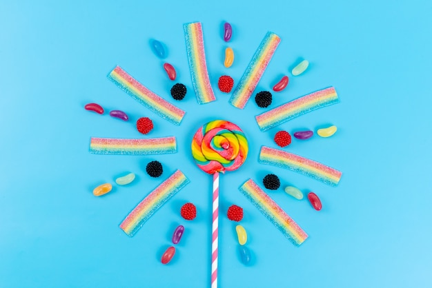 A top view marmalades and lollipops colorful delicious on blue, rainbow color sugar