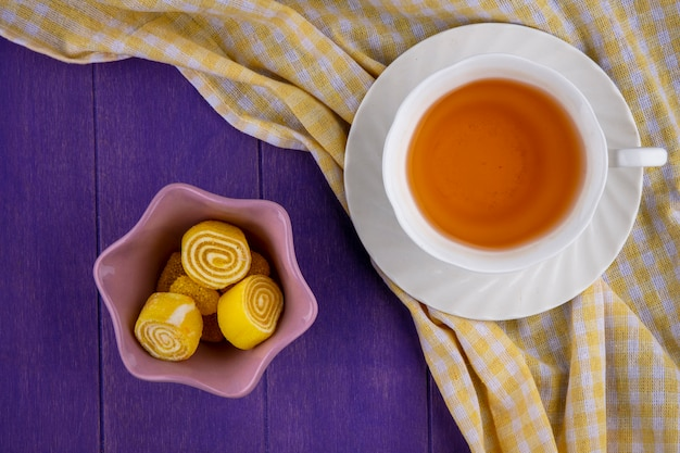 Top view of marmelads in bowl and cup of tea on saucer on plaid cloth and purple background