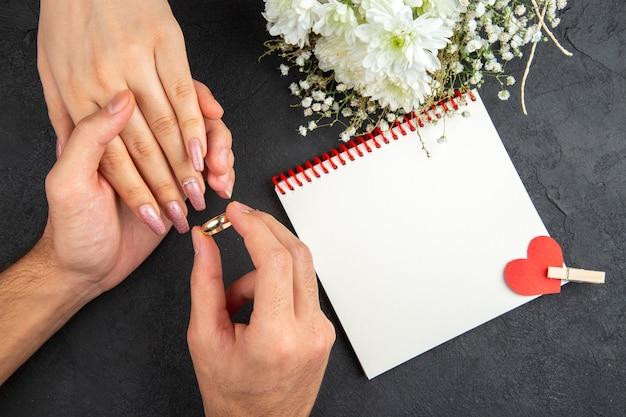 어두운 배경에 여성 손 꽃 노트북에 반지를 배치하는 상위 뷰 결혼 제안 개념 남성 손
