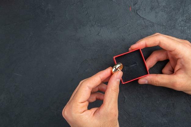 상위 뷰 결혼 제안 개념 남자 손은 여유 공간이 있는 어두운 배경에 결혼 반지와 상자를 들고 있습니다.