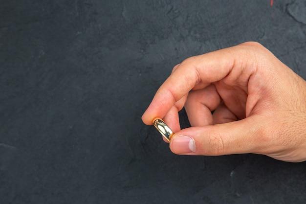 상위 뷰 결혼 제안 개념 남자 손은 여유 공간이 있는 어두운 배경에 결혼 반지를 들고