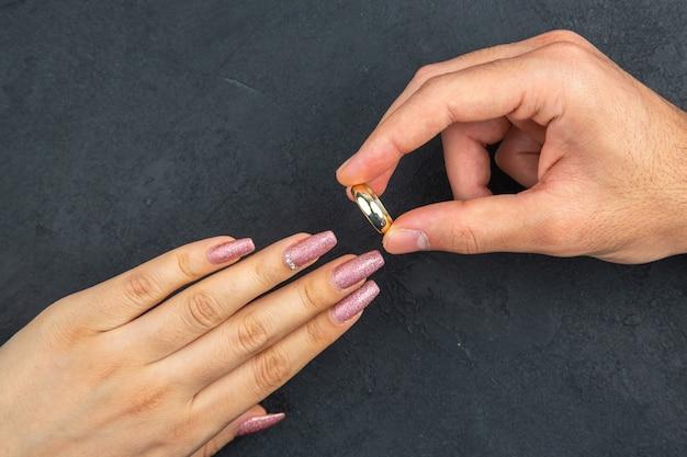 상위 뷰 결혼 제안 개념 남자 손 어두운 배경에 여자 손에 결혼 반지를 배치