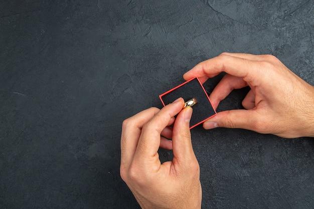 상자에 결혼 반지를 들고 상위 뷰 결혼 제안 개념 남자 손
