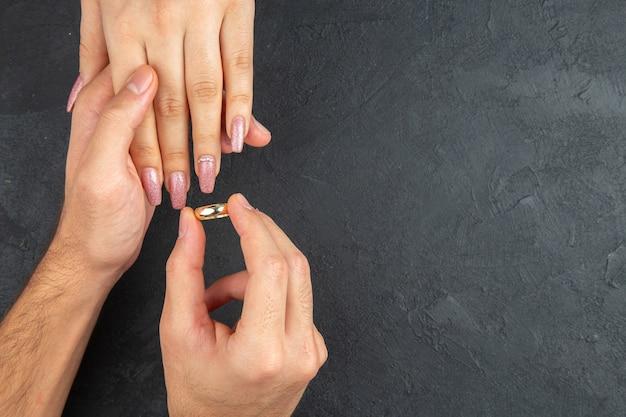 상위 뷰 결혼 제안 개념 남자 손 어두운 배경 복사 장소에 여자 손에 반지를 배치