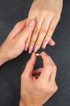 상위 뷰 결혼 제안 개념 남자 손 어두운 배경에 여자 손에 반지를 배치