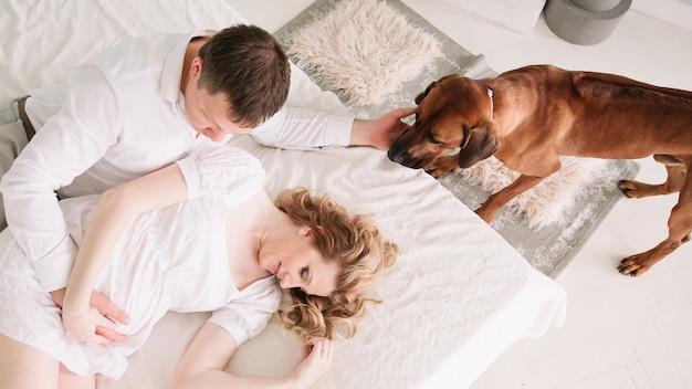 Вид сверху супружеская пара с домашним животным в спальне