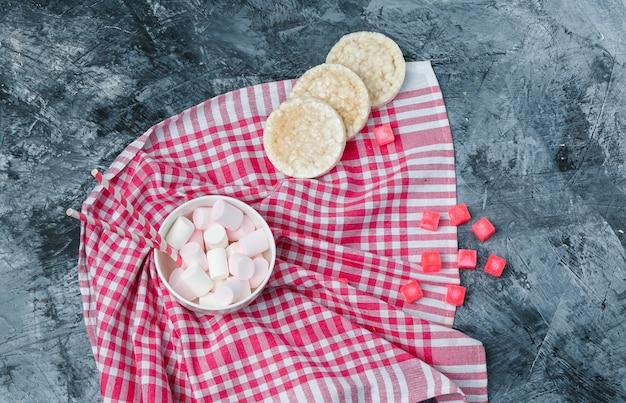 ダークブルーの大理石の表面にライスウエハース、キャンディー、赤いギンガムチェックのテーブルクロスが入ったカップに入ったマシュマロとサトウキビの上面図。水平