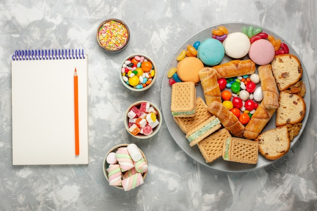 Top view of marshmallows and candies with notepad on white surface