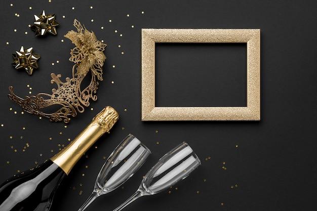 Vista dall'alto della maschera per il carnevale con bottiglia di champagne e cornice
