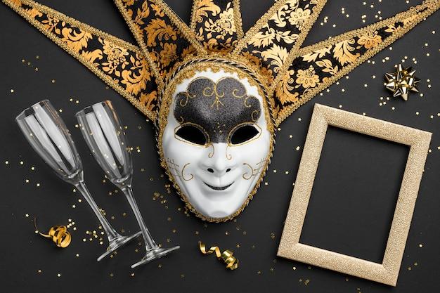 Vista dall'alto della maschera per il carnevale con cornice e bicchieri di champagne