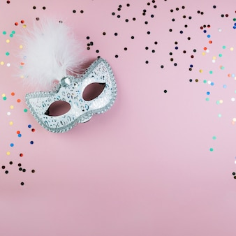 Top view of masquerade carnival mask with colorful confetti on pink background
