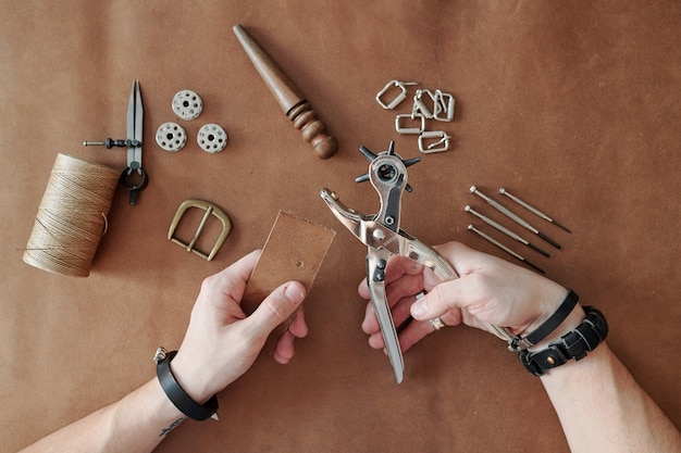 Top view of master hands in bracelets holding handtool for making holes in leather or suede during working process