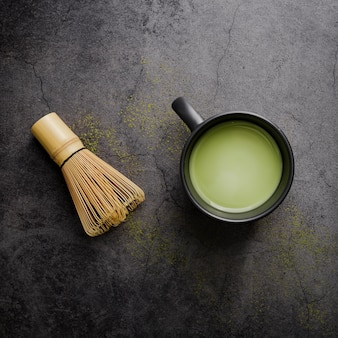 Top view of matcha tea in cup with bamboo whisk