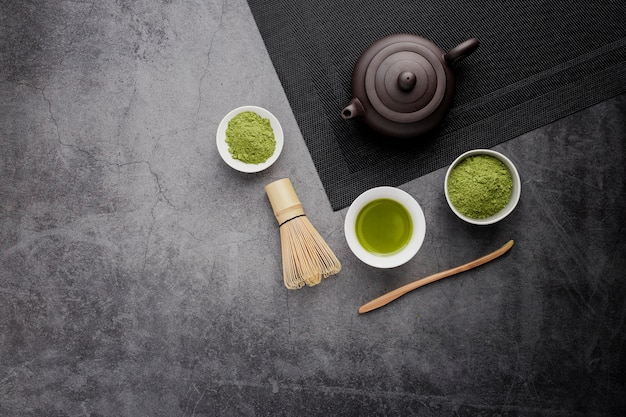 Top view of matcha tea cup with teapot and copy space