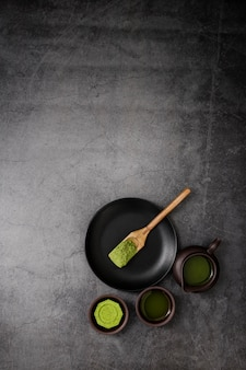 Top view of matcha tea cup with wooden scoop on plate