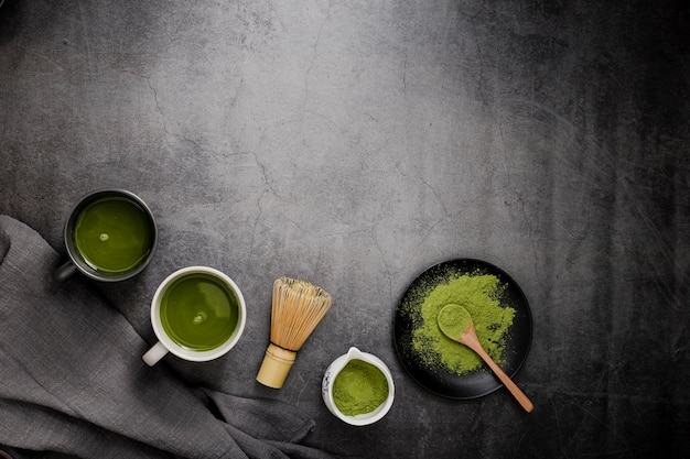Top view of matcha tea in cups with bamboo whisk and copy space
