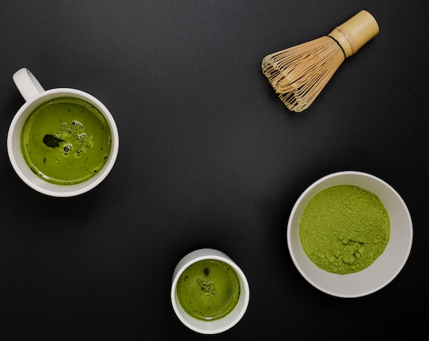 Top view of matcha tea in cups with bamboo whisk