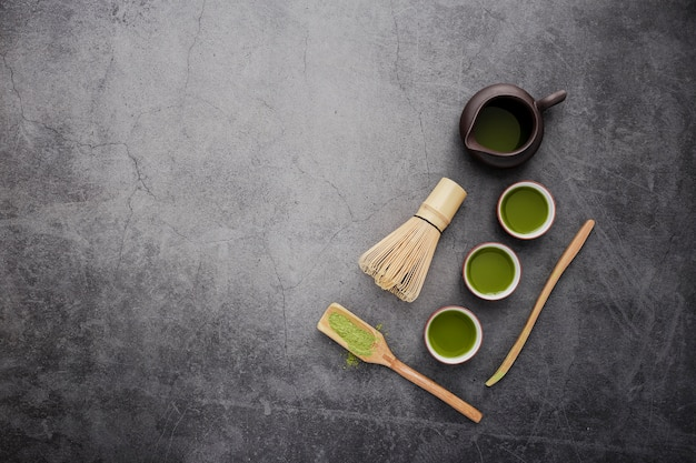 Top view of matcha tea cups with wooden scoop