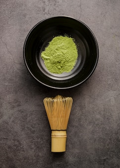 Top view of matcha tea powder in bowl with bamboo whisk