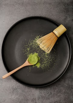 Top view of matcha tea powder on plate with bamboo whisk and spoon