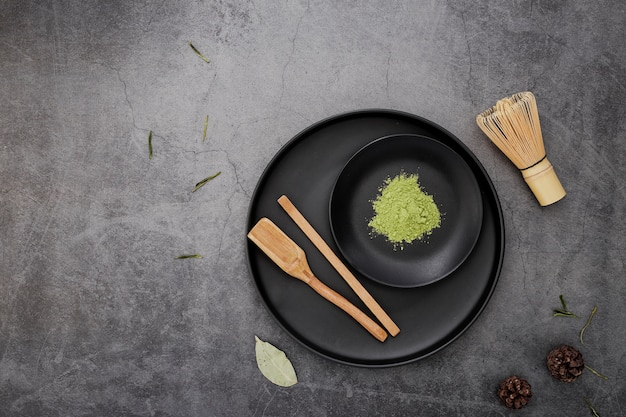 Top view of matcha tea powder with bamboo whisk