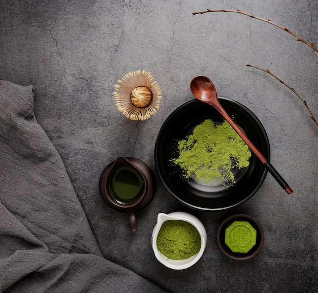 Top view of matcha tea with branches and wooden spoon